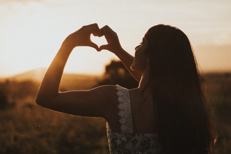 Women holding her hands in a heart shape to symbolise self care