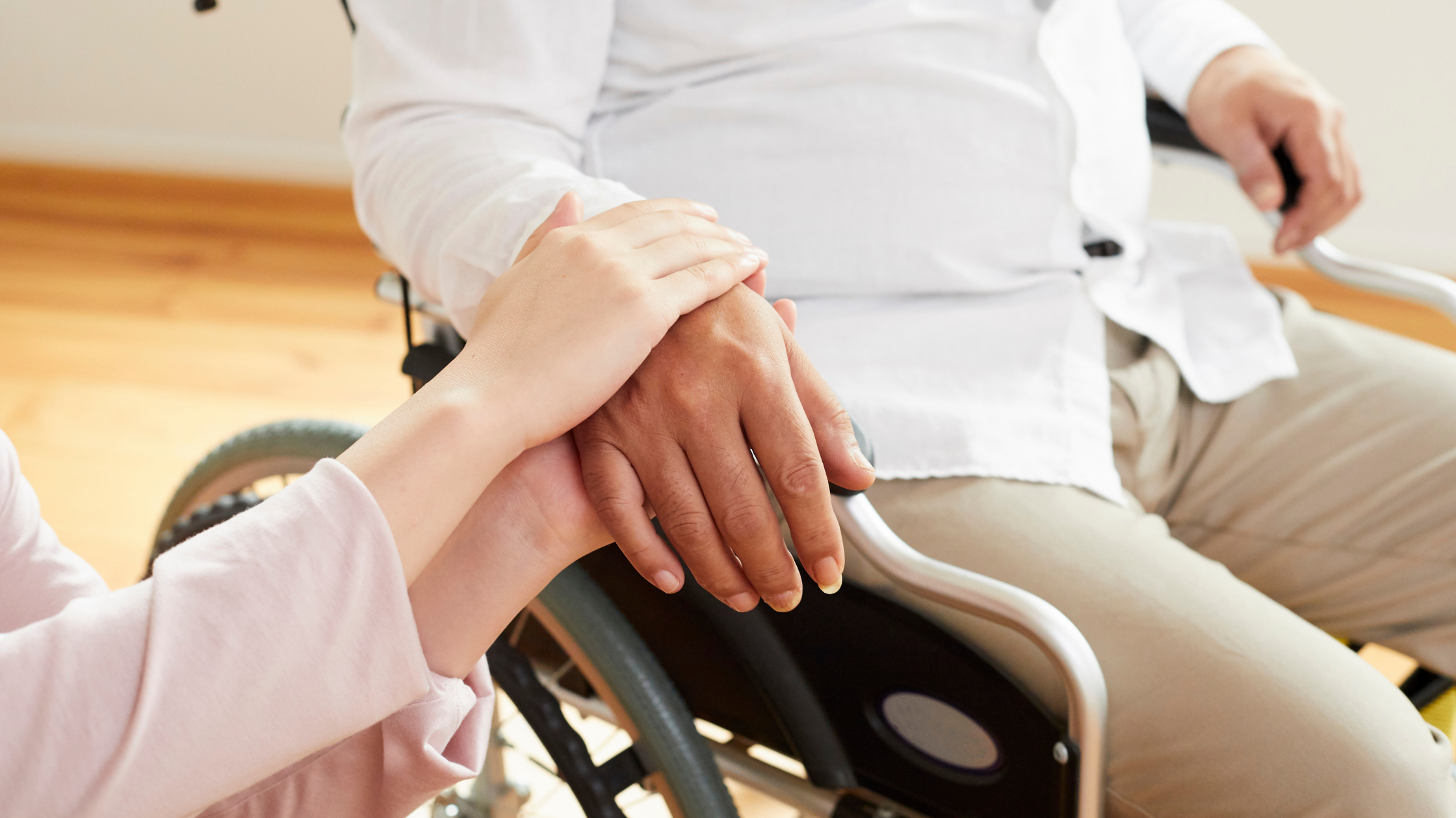 Social Worker consoling a Stroke Recovery Patient by holding their hand